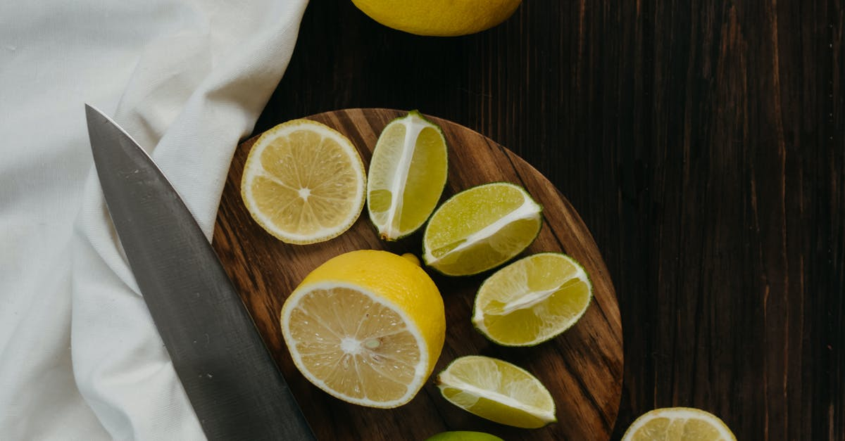 Two oranges sitting on top of a wooden table